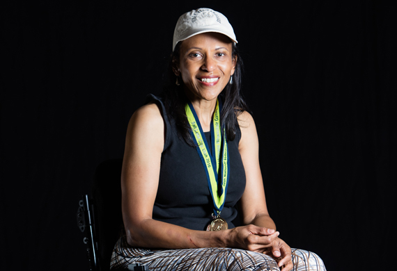 image of Karla Clay posing with her wheelchair games medal